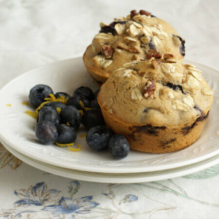 Two Plated Blueberry Muffins with fresh blueberries on the side