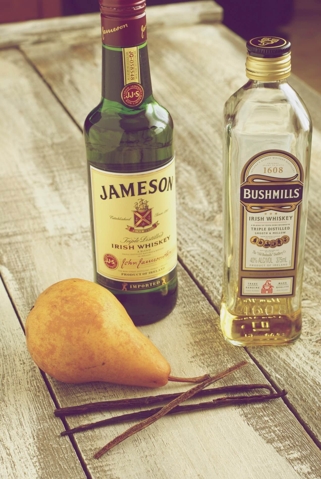 Two bottles of Irish Whiskey with a Boch Pear and Burbon Vanilla Beans