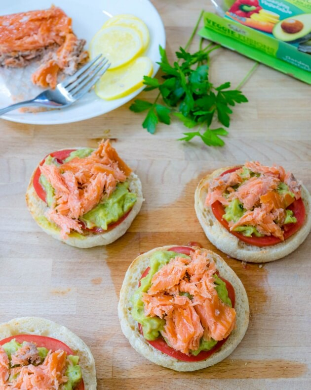 Avocado toast with smoked salmon on crisp toasted English muffins topped with tomato, Sabra's new Veggie Fusions guacamole + veggies is the perfect healthy lunch for busy days.