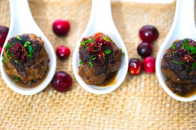 Tender cranberry glazed meatballs dotted with dried cranberries & fresh parsley, pan seared, then simmered in a sweet-tart cranberry glaze.