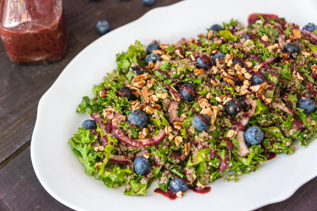 Quinoa Salad with kale, a super-food salad dressed for a party. Topped with crunchy pecans and tangy blueberry dressing. You'll love this make-ahead lunch.