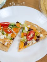 Quick and easy grilled pita pizza topped with hummus and fresh ingredients are healthy and filling. Make for a quick lunch, dinner, or healthy appetizer.